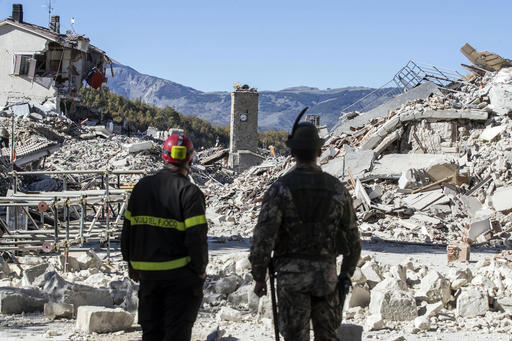 A firefighter, left, andan alpine soldier look at rubble in the hilltop town of Amatrice as an earthquake with a preliminary magnitude of 6.6 struck central Italy, Sunday, Oct. 30, 2016. A powerful earthquake rocked the same area of central and southern Italy hit by quake in August and a pair of aftershocks last week, sending already quake-damaged buildings crumbling after a week of temblors that have left thousands homeless. (Massimo Percossi/ANSA via AP)